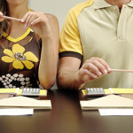 Couple at table in front of calculators and note books pan  e